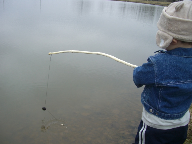 Photo of my son holding his fishing rod over the pond.
